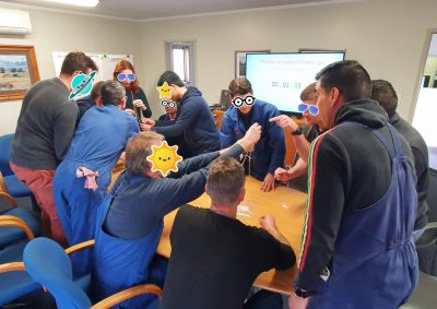 A photo of people doing a workshop activity, with stickers over faces for privacy