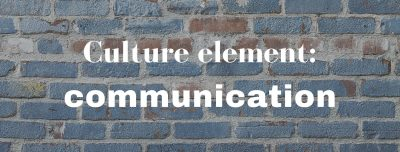 A blue-painted brick wall with the words 'Culture element: communication' superimposed in white
