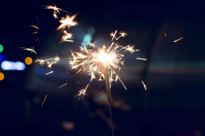 Two sparklers held in a hand against a dark background