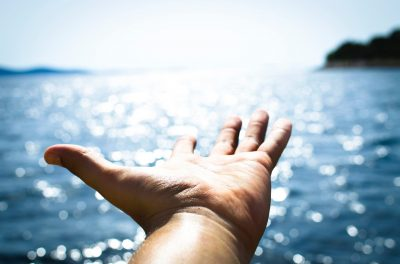 A picture of a hand, palm upward, outstretched towards the horizon, with an ocean in the background..
