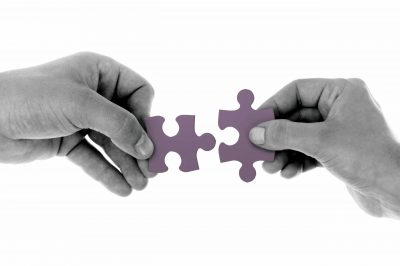 Two hands each holding a jigsaw puzzle piece, ready to fit the pieces together