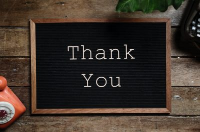 Black noticeboard with white writing saying 'Thank You'