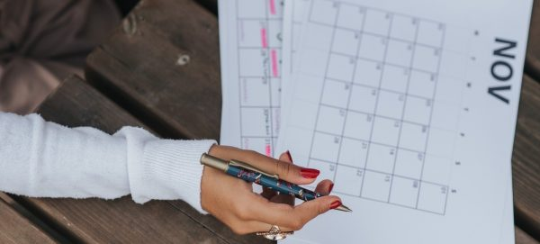 A woman's hand holding a pen above a calendar page