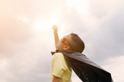 A young boy dressed in a cape and sunglasses, with arm outstretched to the sky.