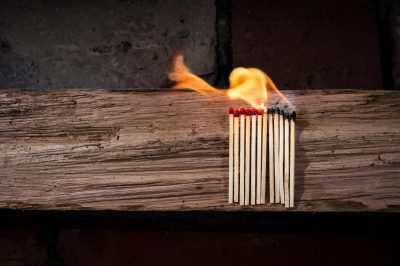 A row of matches on fire, buring from right to left