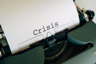 A typewriter with the word 'crisis' in the centre of a white sheet of paper
