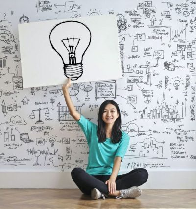 Woman sitting in front of a wall holding a drawing of a light bulb