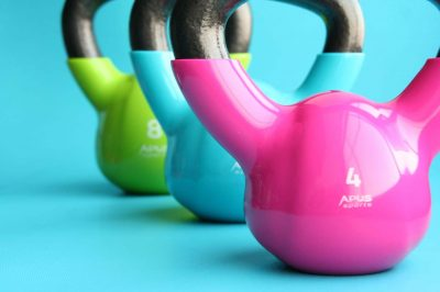 Picture of a pink, blue and green strength-training kettlebell on a blue background